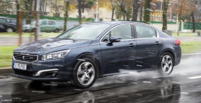 Обновленный седан Пежо 508 2018 модельного года в движении на мокрой дороге