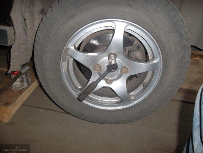 Колесо с литым диском на автомобиле ВАЗ-2110, подготовка для замены сайлентблоков передней балки
