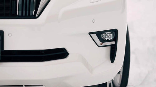 Противотуманная фара в белом бампере кроссовера Тойота Прадо 2018 года выпуска
