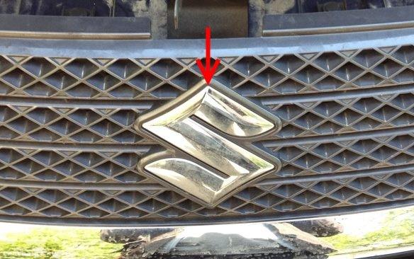 Декоративная решетка с хромированной эмблемой в передней части автомобиля Сузуки Гранд Витара