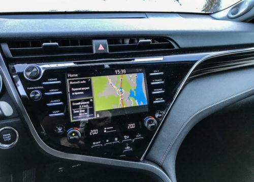 Монитор навигационной системы на передней консоли в салоне бизнес-седана Тойота Камри 2018 года выпуска