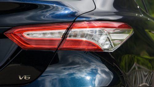 Узкий задний фонарь на кузове седана Тойота Камри 2018 года черного цвета