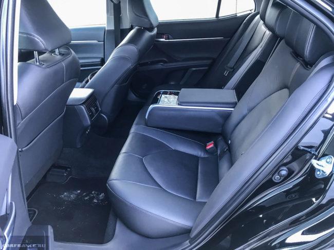 Задний ряд сидений с центральным подлокотников в салоне Тойота Камри 2018 модельного года