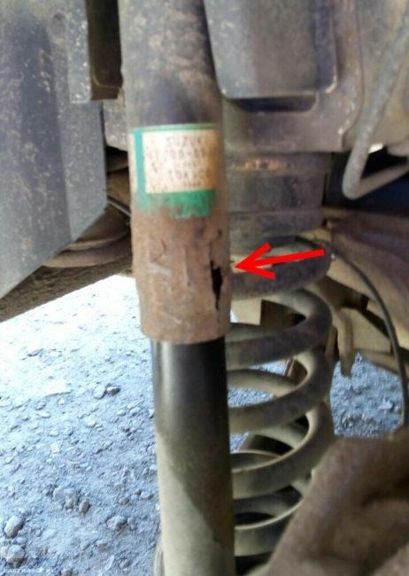 Ржавый кожух на заднем амортизаторе в подвеске автомобиля Сузуки Гранд Витара