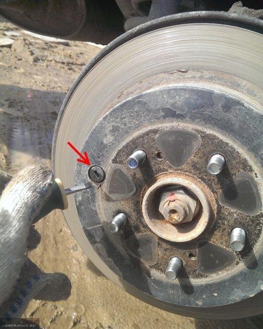 Снятие заглушки отверстия для регулировки схождения колодок в задних дисковых тормозах на Сузуки Гранд Витара