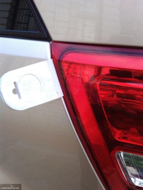 Снятие заднего фонаря с помощью шпателя на автомобиле Сузуки Гранд Витара