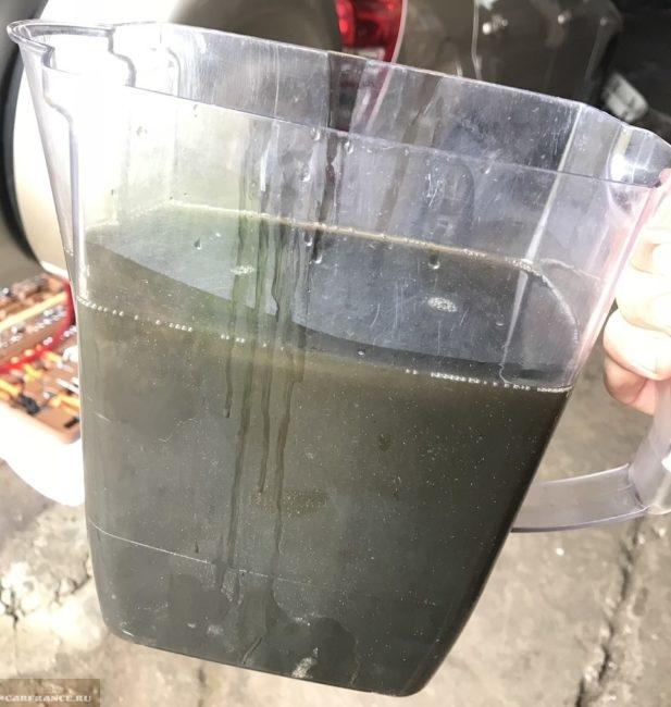 Отработанное трансмиссионное масло черного цвета из раздаточной коробки Сузуки Гранд Витара