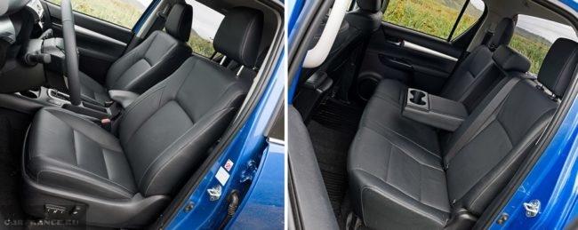 Темная обивка передних и задних сидений в салоне пикапа Тойота Хайлюкс в новом кузове
