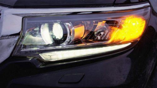 Включенный указатель поворота в передней блок-фаре кроссовера Тойота Прадо 2019 года выпуска