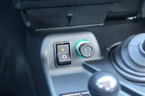 Прикуриватель и кнопка кондиционера на консоли автомобиля Лада Нива 4х4 2019 года