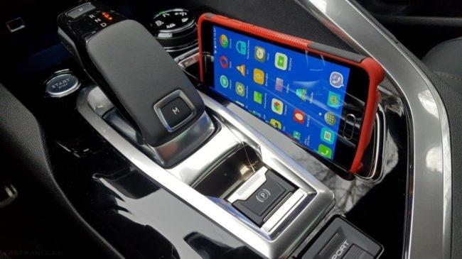 Рукоятка переключения режимов работы автоматической коробки передач в Пежо 3008 и смартфон на зарядке