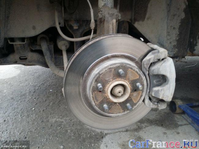 Тормозной диск в передней подвеске Сузуки Гранд Витара без колеса