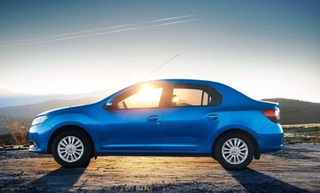Вид сбоку на фоне заката нового Рено Логан в голубом классическом цвете