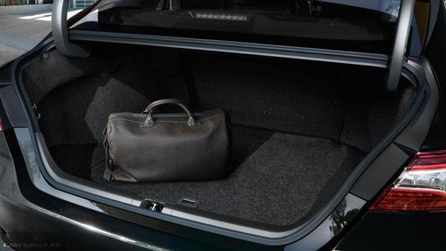 Чёрная сумка на ковровом покрытии багажника в Тойота Камри