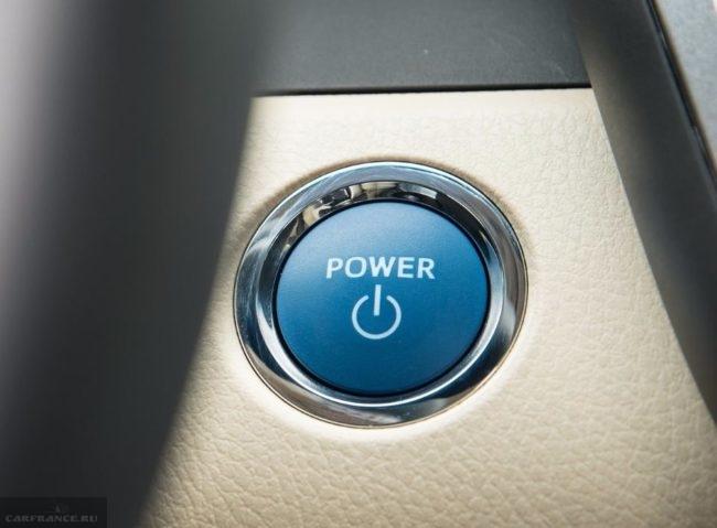 Синяя кнопка запуска двигателя в автомобиле Тойота Камри вблизи