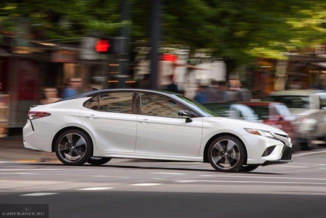 Тойота Камри 2019 модельного года белой окраски на городском перекрёстке