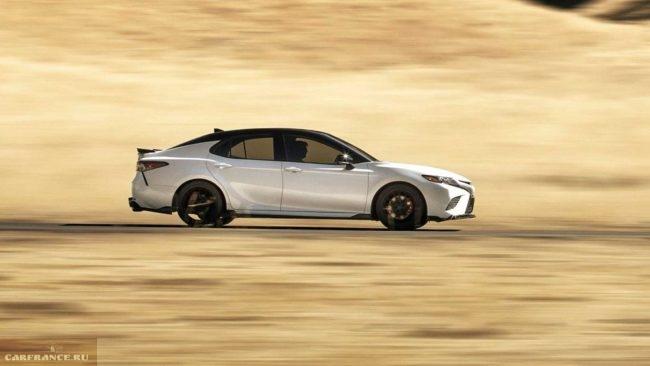 Светлые седан представительского класса Тойота Камри 2019 года выпуска на пустой дороге
