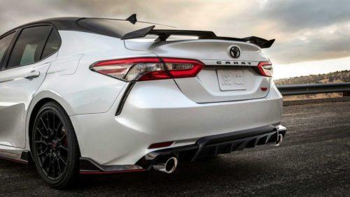 Задний фонарь узкой формы в задней части белого седана Тойота Камри 2019 года