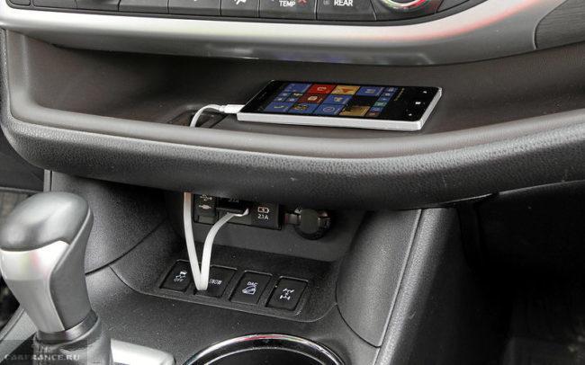 Смартфон на полочке в салоне автомобиля Тойота Хайлендер в последнем кузове