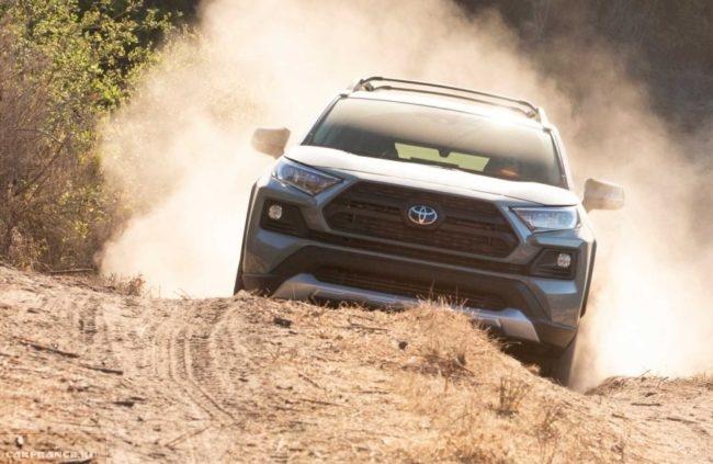 Облако пыли за автомобилем Тойота РАВ 4 в новом кузове при движении по проселку