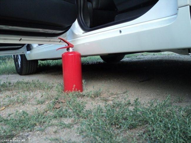 Красный огнетушитель открытой двери автомобиля Тойота Версо 2019 года производства