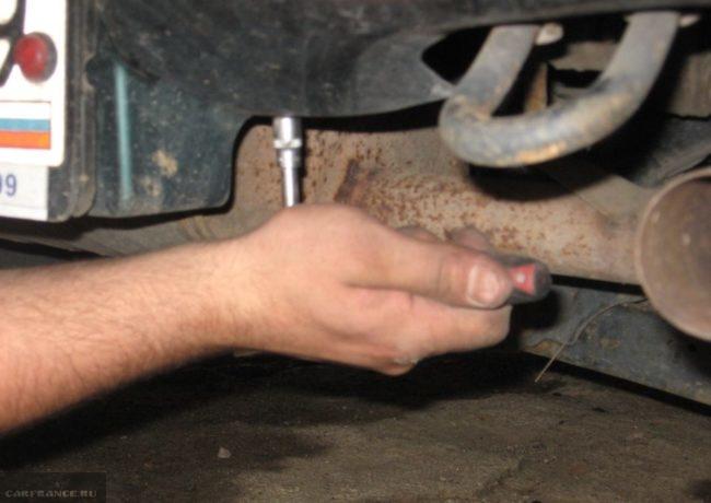 Отворачивание винта нижнего крепления заднего бампера в автомобиле Сузуки Гранд Витара