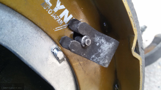 Старая стопорная скоба на новой тормозной колодке заднего колеса седана Фольксваген Поло