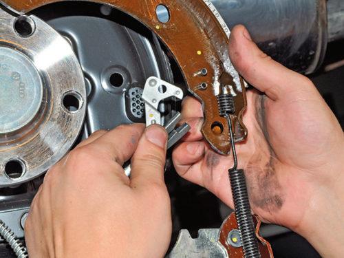 Отсоединение троса стояночного тормоза от колодок на седане Фольксваген Поло
