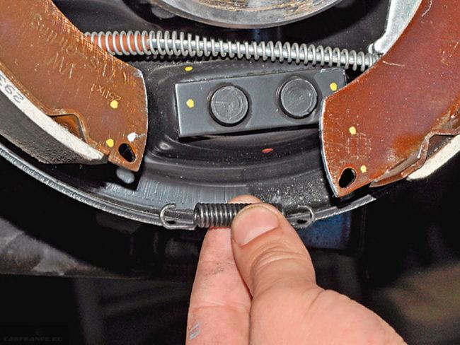 Снятие нижней пружины с тормозных колодок на заднем колесе Фольксваген Поло седан