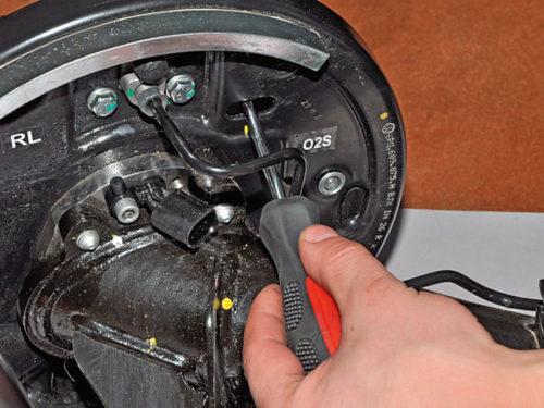 Сведение задних колодок отверткой через технологическое отверстие на барабане автомобиля Фольксваген Поло седан