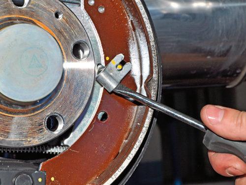 Снятие стопорной скобы тормозной колодки на заднем колесе автомобиля Фольксваген Поло седан