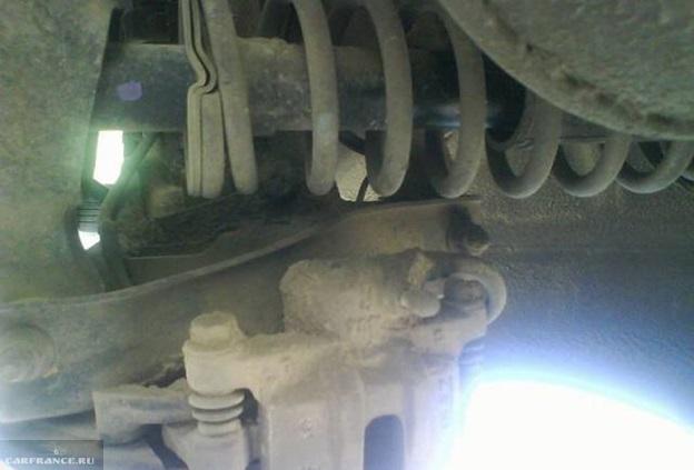Грязное крепление тормозных суппортов на заднем колесе седана Митсубиси Лансер 9