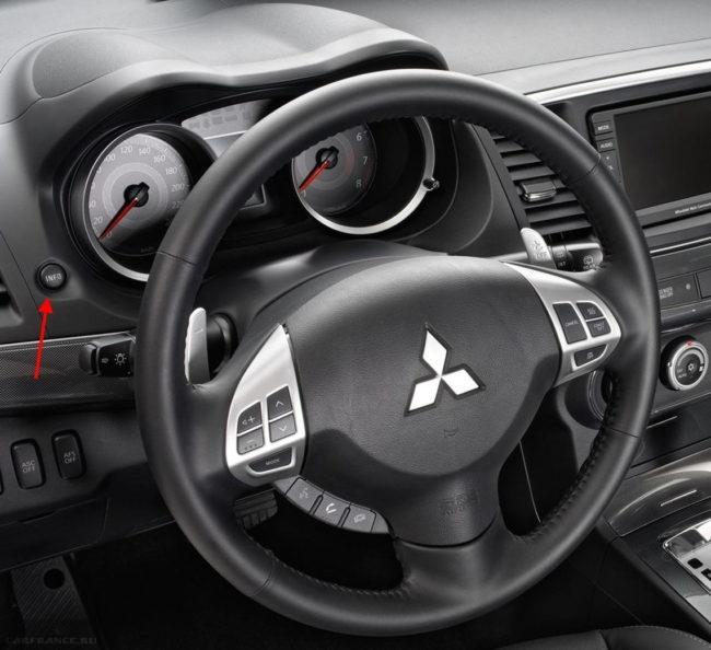 Кнопка INFO на приборной панели в салоне автомобиля Митсубиси Лансер 10