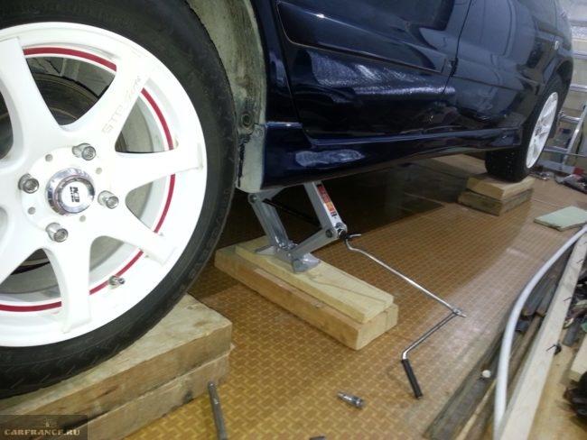 Поднятое на домкрате заднее колесо автомобиля Митсубиси Лансер 9