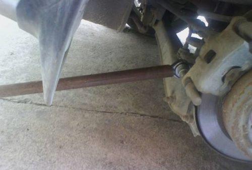Отворачивание нижнего болта заднего тормозного суппорта на Митсубиси Лансер 9 с помощью трубы