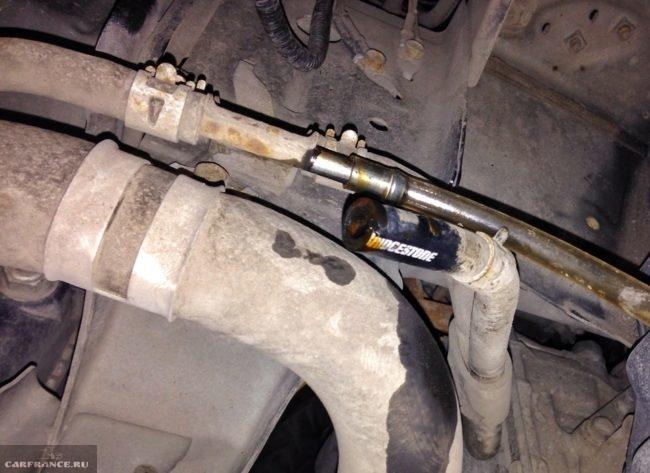 Шланг от радиатора к автоматической коробке передач под днищем автомобиля Мицубиси Лансер 10