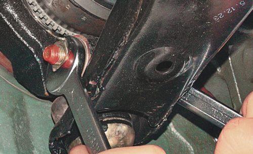 Откручивание фиксирующего болта пальца шарового механизма в передней подвеске Митсубиси Лансер 9