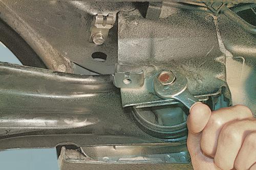 Отворачивание болта крепления продольного рычага к кронштейну на кузове седана Митсубиси Лансер 9