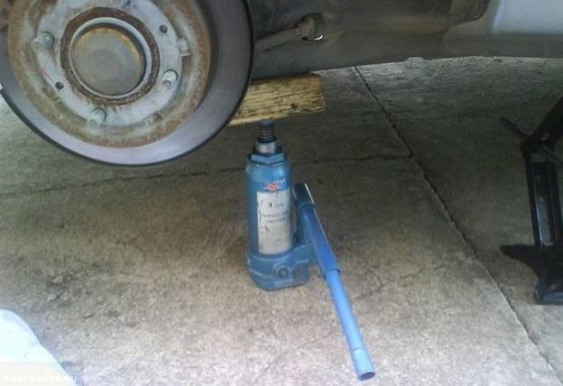 Масляный домкрат под задним колесом автомобиля Митсубиси Лансер 9