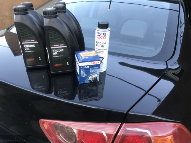 Пять литровых канистр с моторным маслом на багажнике седана Митсубиси Лансер 10