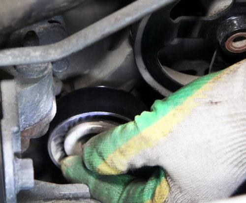 Выворачивание болта крепления обводного ролика на седане Митсубиси Лансер 10 с двигателем 1.5