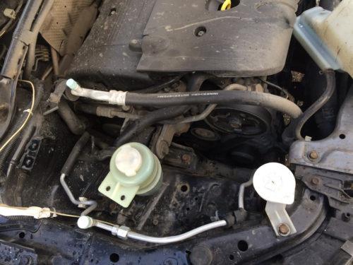 Моторный отсек автомобиля Митсубиси Лансер 10 со снятым расширительным бачком