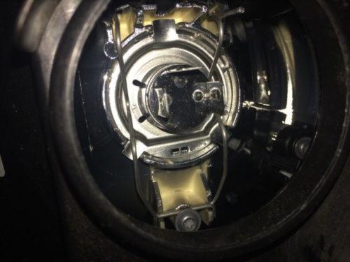 Пружинный фиксатор на цоколе лампы ближнего света в Фольксваген Поло седан