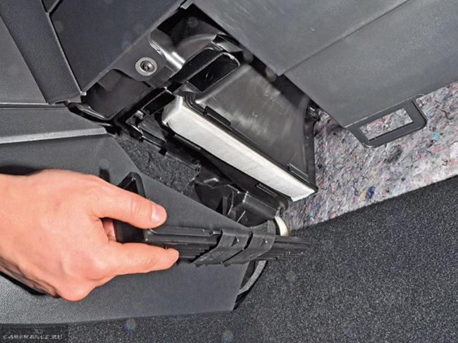 Снятие крышки фильтра в салоне седана Фольксваген Поло с двигателем 1,6 литра