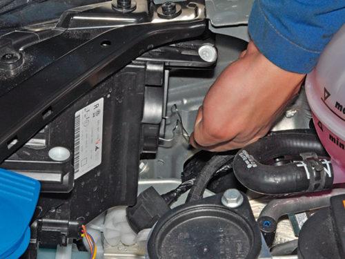 Отсоединение фиксатора лампы ближнего света под капотом Фольксваген Поло седан