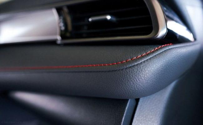 Красные нитки на кожаном подлокотнике в салоне Тойота Камри 2020 года выпуска